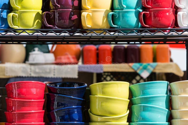 Pilas coloridas de tazas y de cuencos genéricos de café en el mercado imágenes de archivo libres de regalías