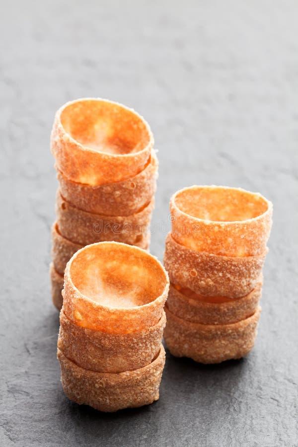 Pilas de cajas curruscantes de los pasteles de los croustades en backgro de piedra negro foto de archivo