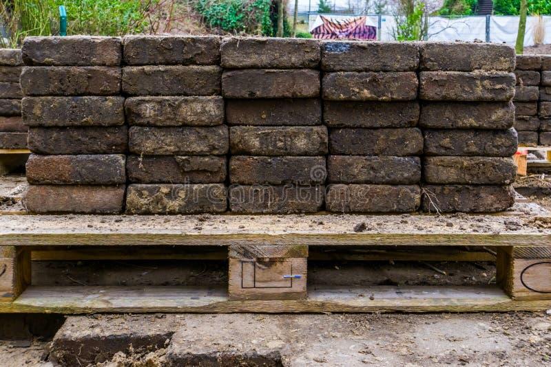 Pilas de calle que pavimentan apiladas en una plataforma, fondo del sector de la construcción fotografía de archivo