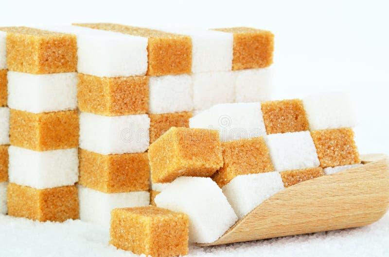 Pilas de cubos del azúcar marrón y blanco imagen de archivo