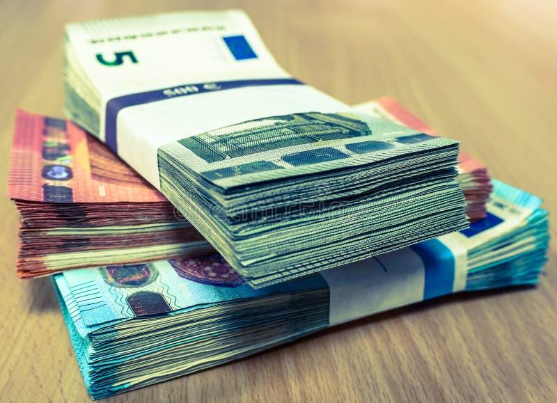 Pilas de cuentas euro en un escritorio del pino en fives, diez y años 20 imagen de archivo