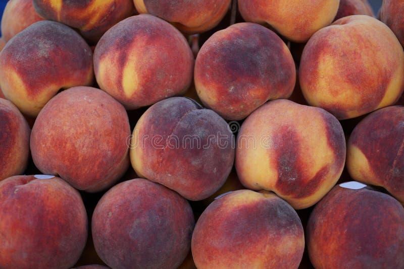 Pilas de fondo jugoso dulce fresco estacional del melocotón del color de la pendiente en mercado de la fruta local de la ciudad foto de archivo libre de regalías