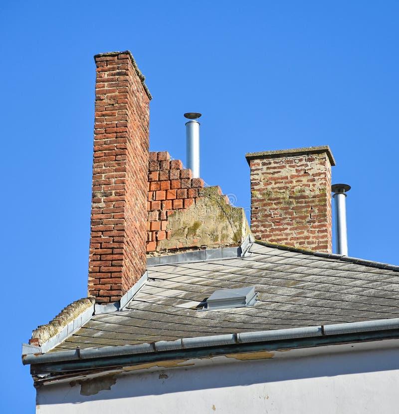 Pilas de humo en el tejado de un edificio viejo imágenes de archivo libres de regalías