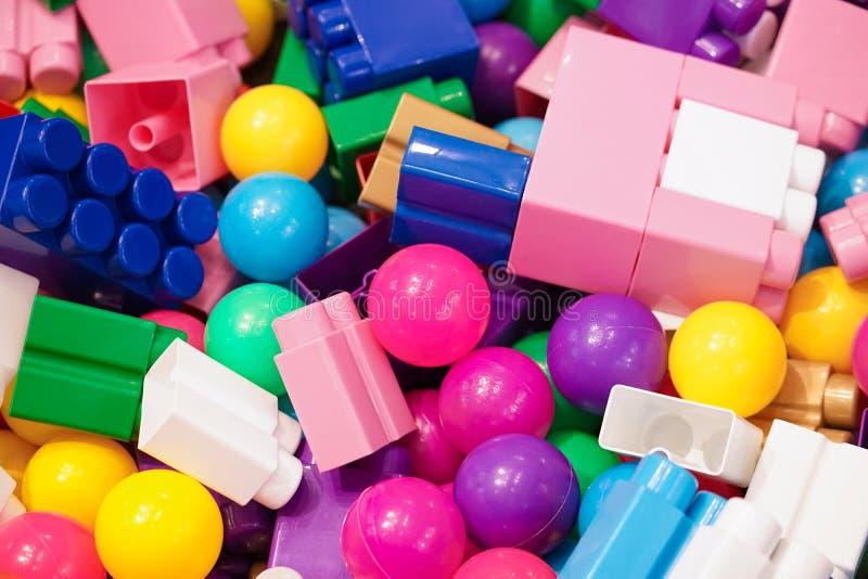 Pilas de juguetes Muchos juguetes coloridos incluyendo bolas y juguetes o unidades de creación plásticos, visión superior de la c foto de archivo