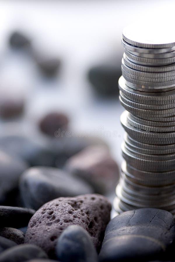 Pilas de la moneda en un fondo blanco con las piedras - profundidad del campo macra imagenes de archivo