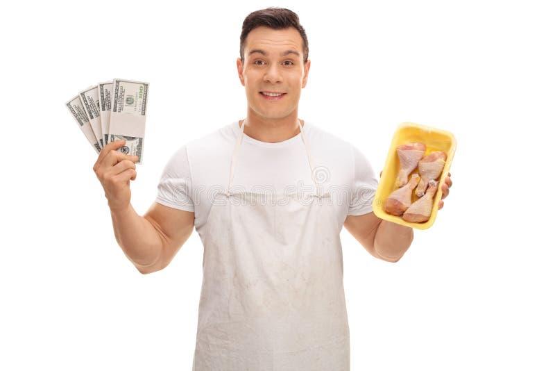 Pilas de la tenencia del carnicero de tambores del dinero y del pollo imagen de archivo libre de regalías