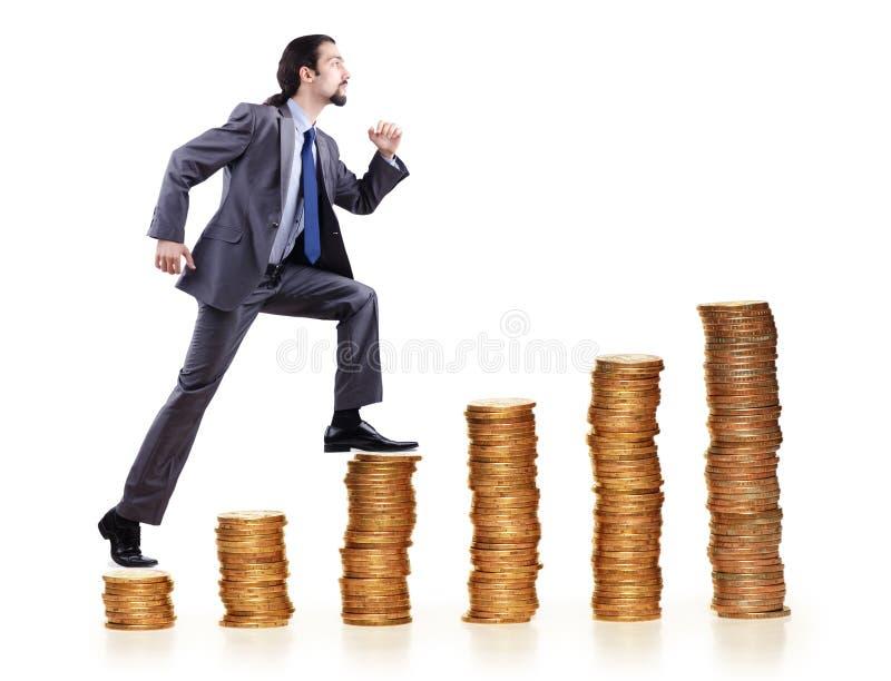 Pilas de las monedas del hombre de negocios que suben imagen de archivo