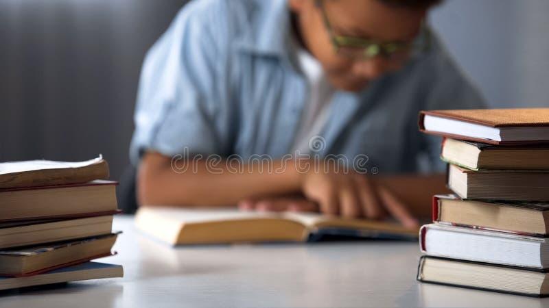 Pilas de libros en la tabla del alumno, sistema educativo, afición temprana del desarrollo infantil imagenes de archivo