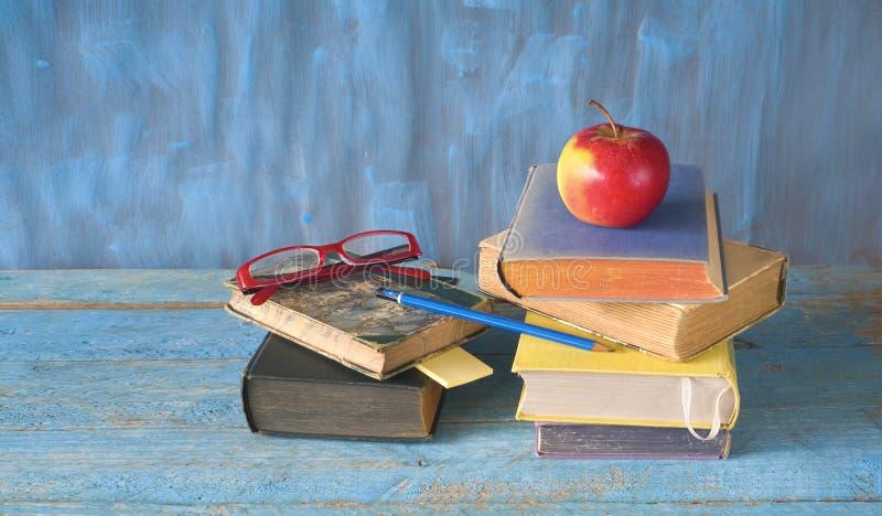 Pilas de libros, de manzana, de gafas y de pluma, lectura, educación, de nuevo a concepto de la escuela, fotografía de archivo libre de regalías