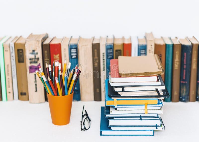Pilas de los cuadernos, pila de educación de los libros de nuevo a fondo de la escuela, libros de texto, vidrios y lápices en ten fotografía de archivo libre de regalías