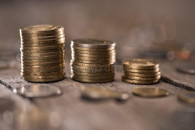 Pilas de monedas en el tablero de la mesa de madera fotos de archivo libres de regalías
