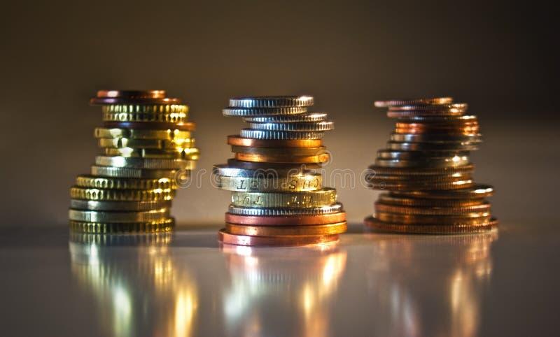 Pilas de monedas: LOS E.E.U.U., REINO UNIDO, UE fotografía de archivo