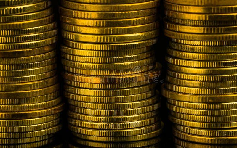Pilas de oro de la moneda del color en fondo oscuro con el espacio de la copia para el texto Crecimiento del negocio y de las fin fotografía de archivo