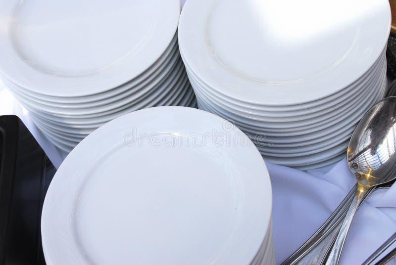 Pilas de placas del abastecimiento con las cucharas foto de archivo