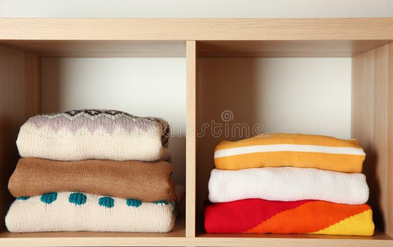 Pilas de ropa doblada del invierno en estantes fotografía de archivo libre de regalías