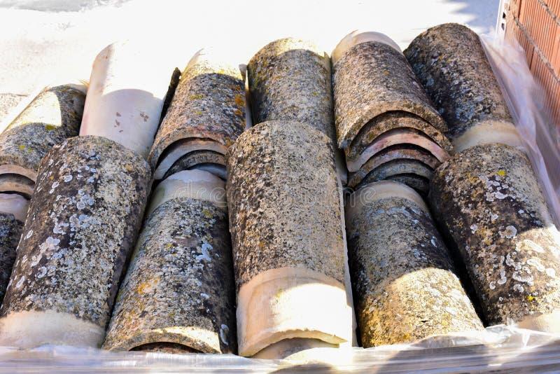 Pilas de tejas de tejado viejas en muchas filas con diverso número en cualquier columna Las tejas antiguas se manchan con polvo y foto de archivo