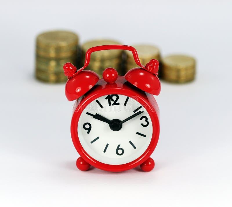 Pilas de tiempo y de dinero foto de archivo