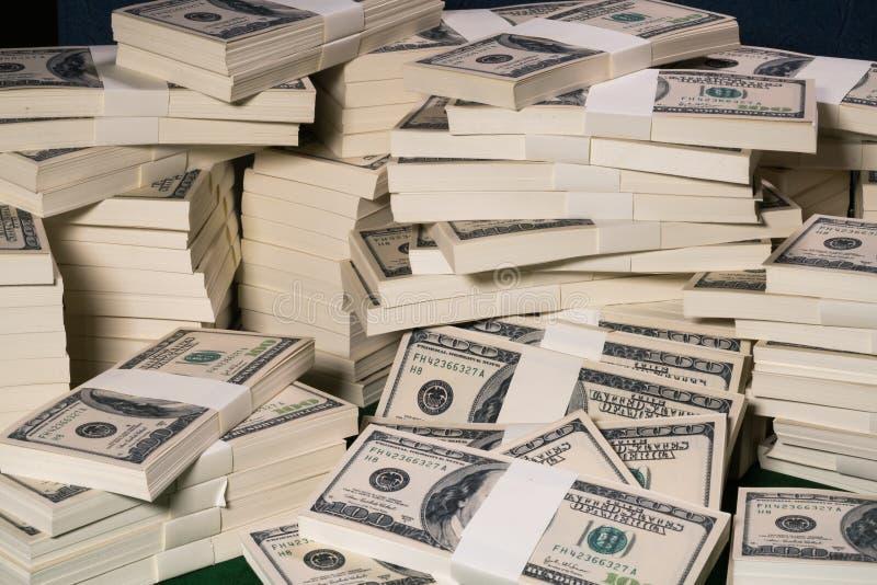 Pilas de un millón dólares de EE. UU. en cientos billetes de banco del dólar imagen de archivo