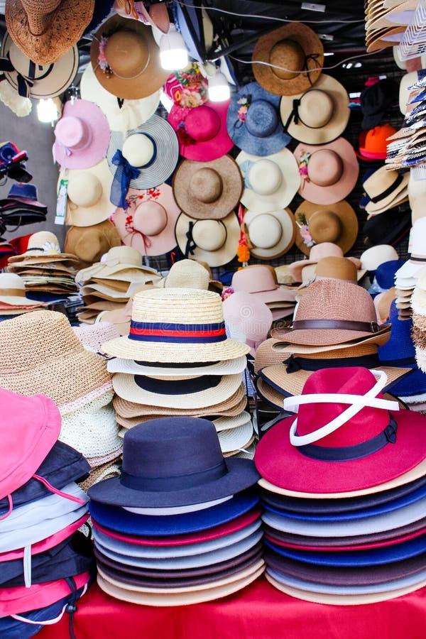 Pilas multicoloras coloridas de sombreros del verano en venta en el mercado callejero de la noche fotos de archivo
