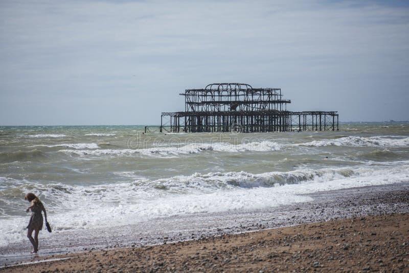 Pilastro ad ovest, Brighton, Inghilterra - la struttura e una ragazza sul beahc fotografia stock libera da diritti
