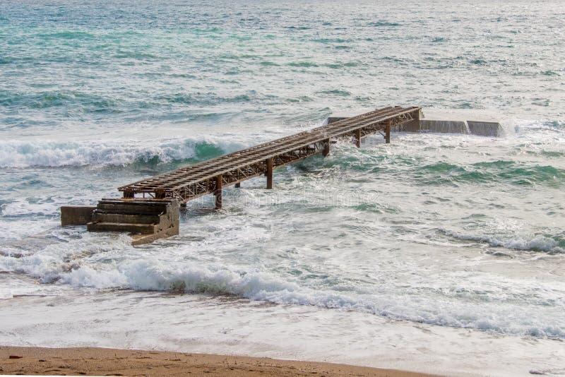 Pilastro arrugginito sui precedenti del mare e delle onde immagine stock