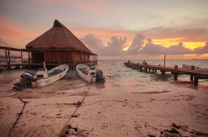 Pilastro, case del trampolo e barche attraccati al tramonto fotografia stock libera da diritti