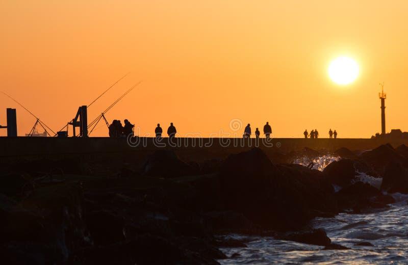 Pilastro con pesca e camminare della gente fotografie stock libere da diritti