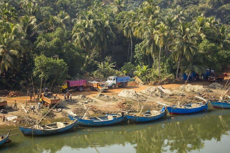 Pilastro del fiume con le barche vuote blu i precedenti della giungla verde della palma e sabbia di carico in immagini stock libere da diritti