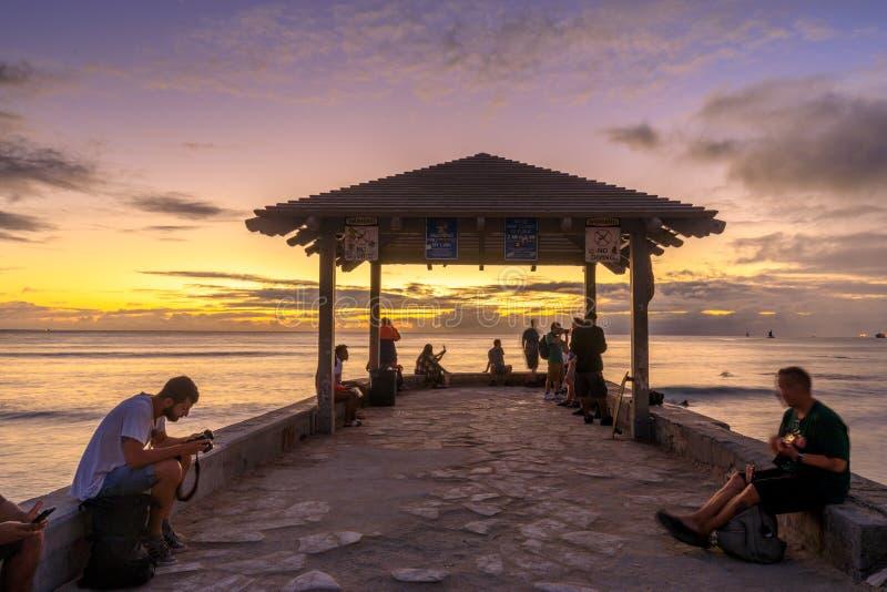 Pilastro delle pareti della spiaggia di Waikiki ad un tramonto dorato di ora fotografia stock