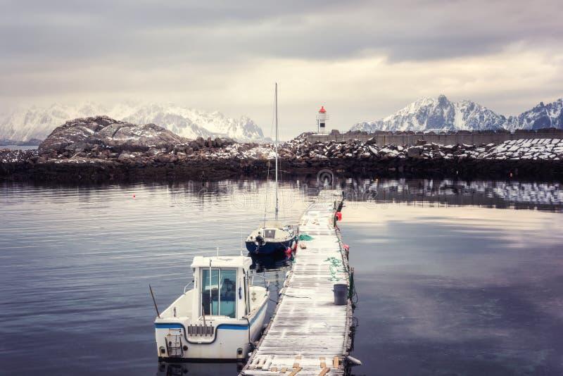 Pilastro di legno con i pescherecci, il faro e le montagne nevose, paesaggio di inverno, Kabelvag, isole di Lofoten, Norvegia immagini stock libere da diritti