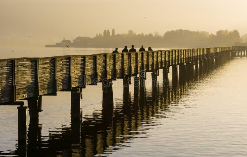 Pilastro di legno lungo del sentiero costiero sopra acqua alla luce uguagliante dorata con una siluetta di camminata del paesaggi fotografie stock