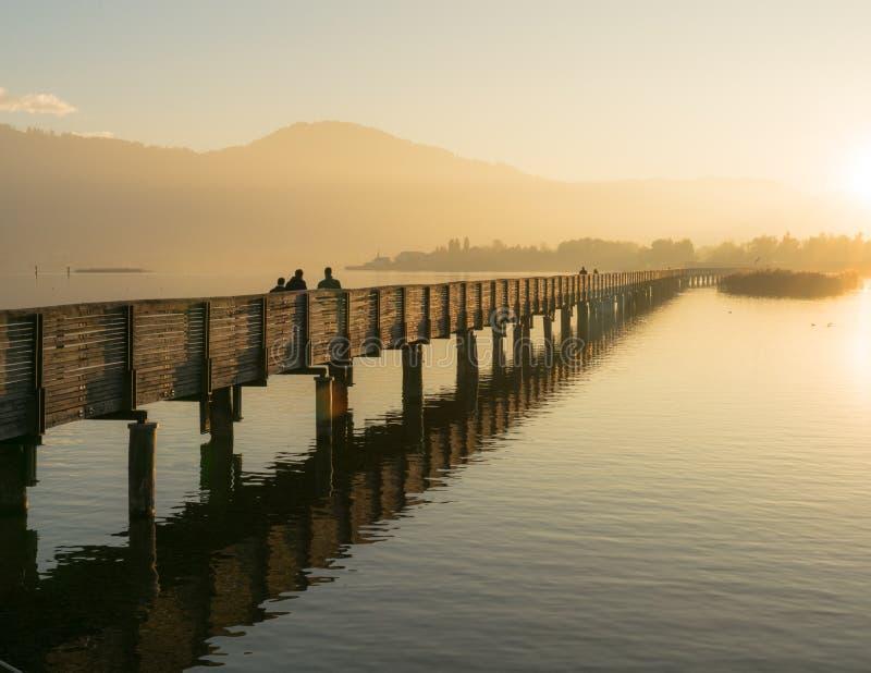 Pilastro di legno lungo del sentiero costiero sopra acqua alla luce uguagliante dorata con una siluetta di camminata del paesaggi immagine stock
