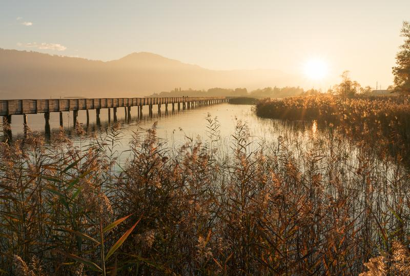 Pilastro di legno lungo del sentiero costiero sopra acqua alla luce uguagliante dorata con una siluetta del paesaggio della monta fotografia stock libera da diritti