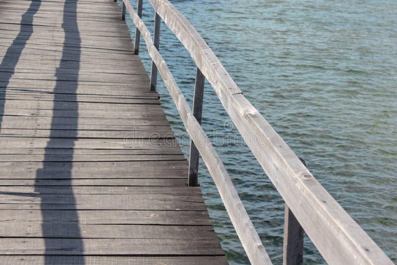 Pilastro di legno sopra acqua calma immagine stock