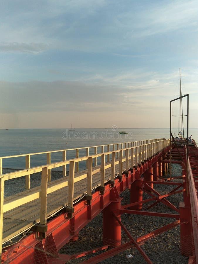 Pilastro di legno su un supporto rosso del metallo sulla costa di mare immagini stock libere da diritti