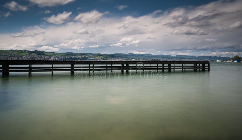 Pilastro di legno sul lago Zurigo con il paesaggio e le barche a vela della montagna di Rolling Hills nei precedenti fotografie stock