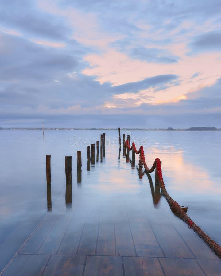 Pilastro di Palafitic sommerso alla corda rossa del briciolo di tramonto ed al cielo rosa fotografie stock libere da diritti