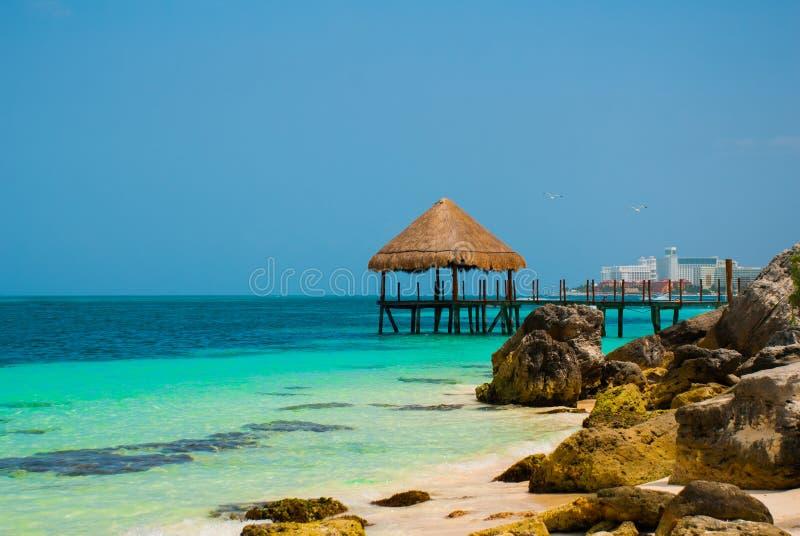 Pilastro e gazebo di legno dalla spiaggia Paesaggio tropicale con il molo: mare, sabbia, rocce, onde, acqua del turchese Il Messi fotografie stock libere da diritti