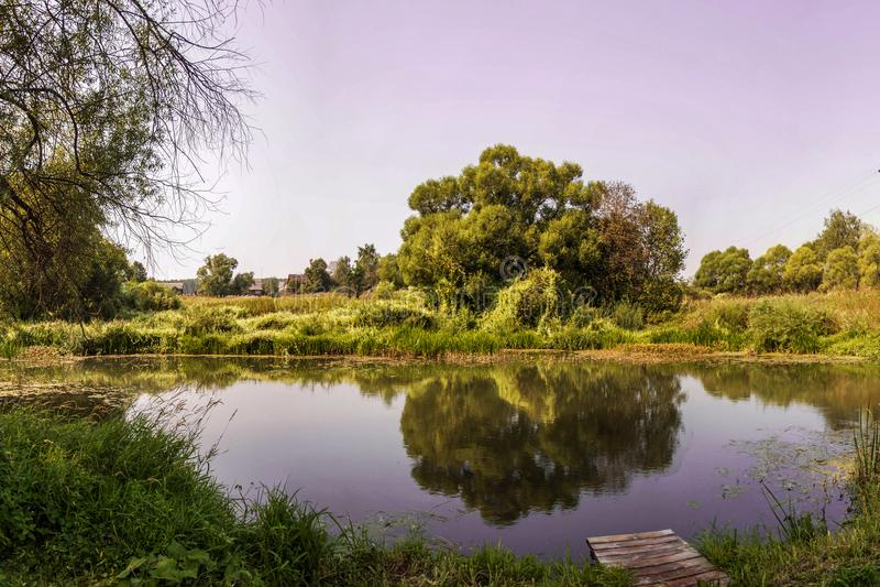 Pilastro su un fiume calmo di estate Ponte di legno del pilastro di mattina Posto per la pesca nel fiume fotografia stock