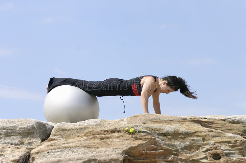 Pilate Pushups. A woman does push ups with a pilates ball royalty free stock photography