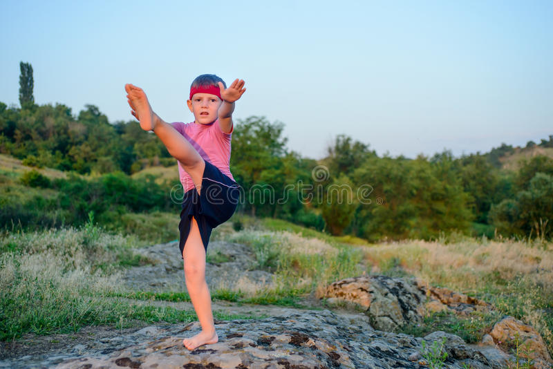 Pilates изгибчивого молодого мальчика практикуя outdoors стоковое фото rf