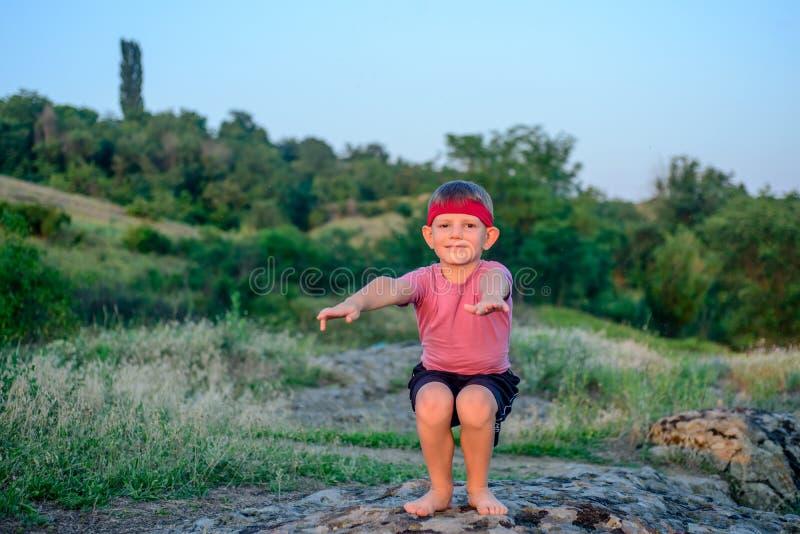 Pilates изгибчивого молодого мальчика практикуя outdoors стоковое изображение