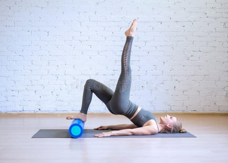 Pilates?? 做在算术的灰色体育衣服的妇女锻炼与健身路辗,顶楼样式背景,被定调子 库存图片