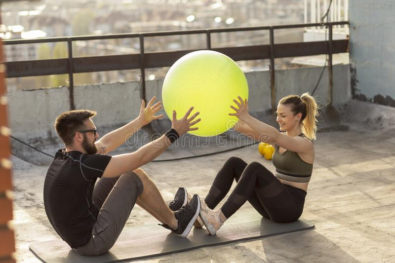 Pilates ball passing exercise. Couple sitting on a yoga mat on a building rooftop terrace, exercising with a pilates ball stock photography