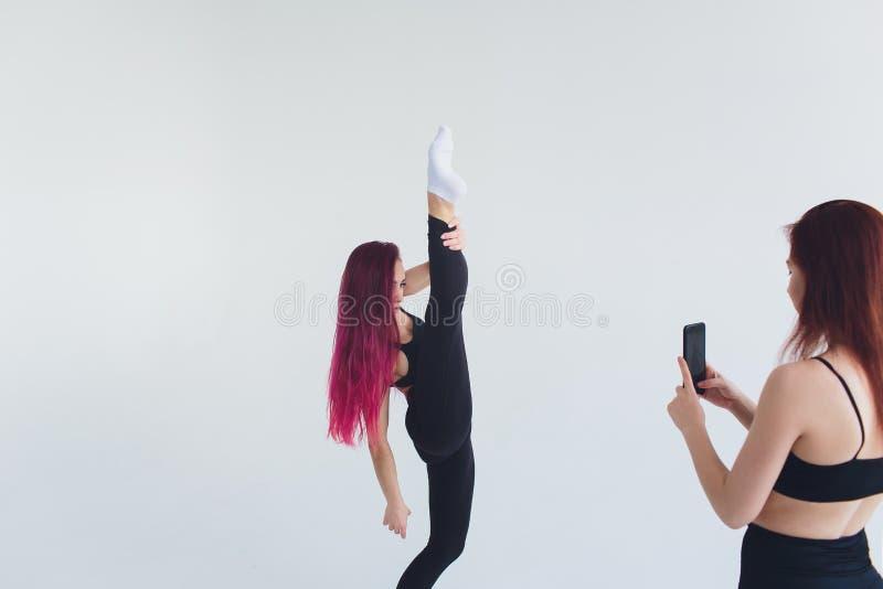 女孩体育健身瑜伽pilates carimat行使体操智能手机席子在米黄背景的carimat锻炼 图库摄影