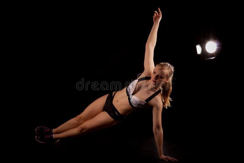 Pilates da ioga do exercício da prancha do lado da menina do esporte fotografia de stock royalty free