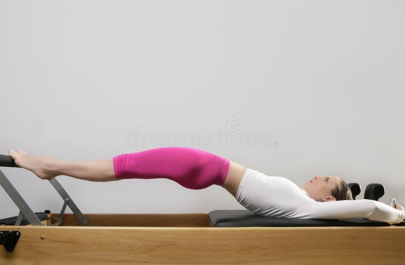 Pilates da mulher da ginástica que esticam o esporte na cama do reformista foto de stock