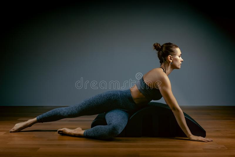 Pilates, fitness, sport, training and people concept - woman doing exercises on a small barrel. Fitness concept, low key royalty free stock image