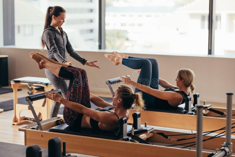 Pilates instruktör som instruerar kvinnor på idrottshallen royaltyfria foton