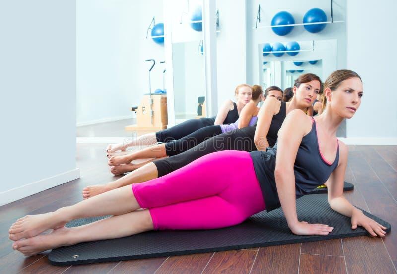 Pilates kvinnagrupp på matt idrottshallinstruktör royaltyfri fotografi